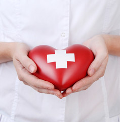 Red heart with cross sign in doctor hand, close-up