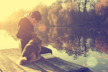 Woman relaxing with dog in sunset at the lake