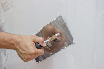 man hand with trowel plastering a wall