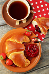 Breakfast with tea and  big fresh croissant on wooden