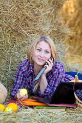 Девушка на сеновале разговаривает по телефону летним днем