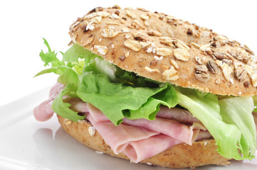 brown bagel filled with ham and lettuce mix