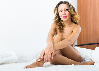 Nude woman posing on bed