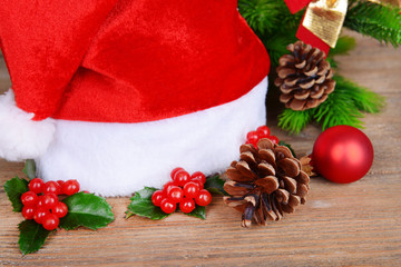 Leaves of mistletoe with Christmas hat on table close-up