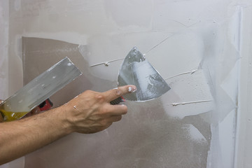 man hand with trowel plastering a wall 2