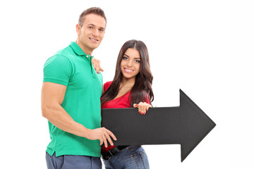 Young couple holding an arrow pointing