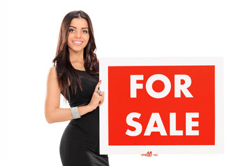 Young woman holding a for sale sign