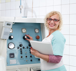 Smiling female specialist tuning medical equipment in laboratory