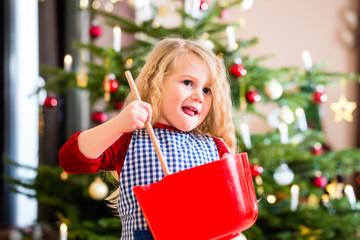 Mädchen backt in der Küche Kekse vor Weihnachtsbaum
