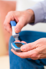 Senior mit Diabetes benutzt Blutzuckermessgerät