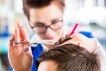 Friseurin schneidet Mann die Haare im Herrensalon