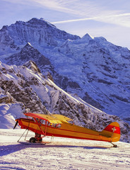 Yellow red airplane at the mountain airfield in front of peaks i