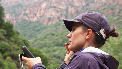 Young woman holding GPS navigator and talking on the phone