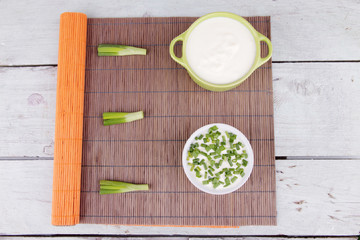 Green pan and plastic bowl of cream with onion