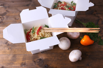 Chinese noodles in takeaway boxes with mushrooms and parsley