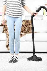 Young woman with vacuum cleaner in room