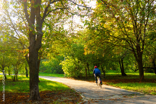 canvas print picture Boy riding bicycle on the park alley in the autumn