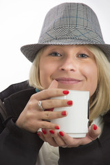 Young woman with a hat and a white cup