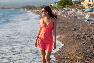 young beautiful woman girl walking along the beach, sunset time