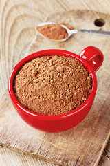 Cocoa powder in a red cup with a spoon on a rustic wooden table