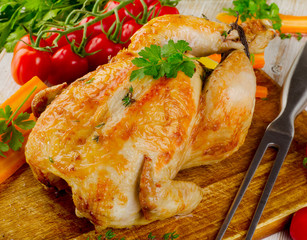 Roasted chicken with vegetables on  a wooden board.