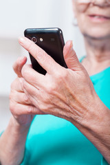 Senior woman sending text message