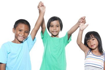 Three kids celebrating with arms up