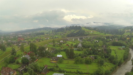 Rural mountain  with  village in cloudy day .Aerial lateral