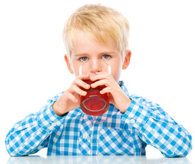 Little boy with glass of cherry juice