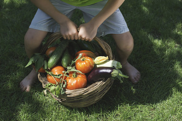 Child and basket with vegetables.