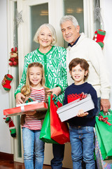 Großeltern und Enkel mit Geschenken an Weihnachten