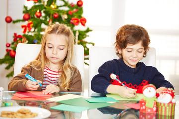 Geschwister malen Grußkarten an Weihnachten