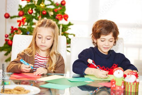 Leinwanddruck Bild Geschwister malen Grußkarten an Weihnachten