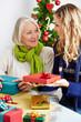 Frau gibt Seniorin Geschenk zu Weihnachten