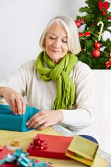 Seniorin verpackt Geschenk für Weihnachten
