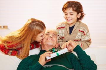 Mädchen küsst Opa mit Geschenk an Weihnachten