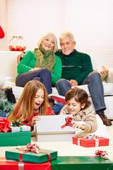 Kinder öffnen Geschenke zu Weihnachten