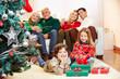 Familie mit Geschenken am Weihnachtsbaum zu Weihnachten