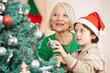 Kind mit Oma hängt Christbaumkugel an Weihnachtsbaum