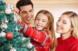 Eltern und Kind schmücken Weihnachtsbaum zu Weihnachten