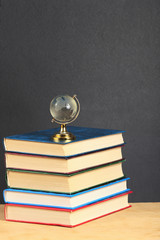 Pile of books and globe on wooden surface.