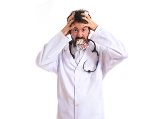 Crazy doctor with pills over white background