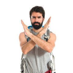 Backpacker doing NO gesture over white background