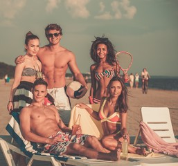 Group of multi ethnic friends with ball and racket on a beach