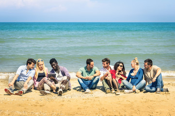 roup of international best friends sitting at beach talking with