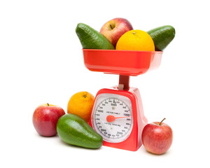 kitchen scales and fresh fruit on a white background