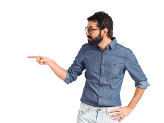Young hipster man pointing lateral over white background