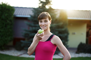 Young sporty woman eating green apple