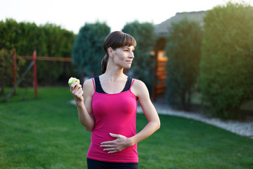Hungry sporty woman with apple