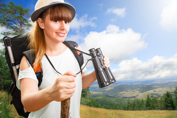 young beautiful woman hiker looking through binocular on mountai